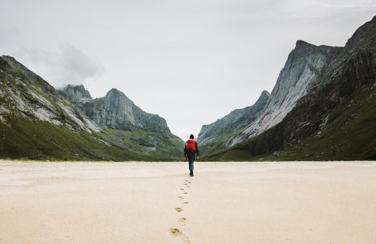 Man walking on beach with mountains in the background